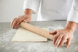 Раскатайте слоеное тесто скалкой на сахаре
